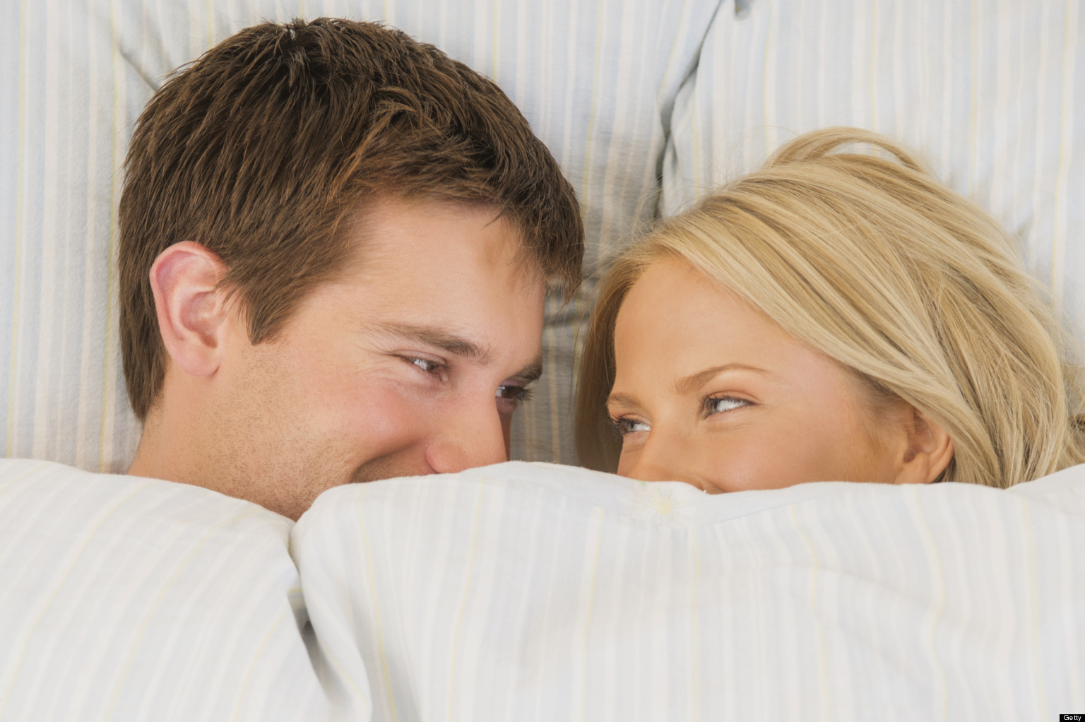 Close up of couple laughing in bed