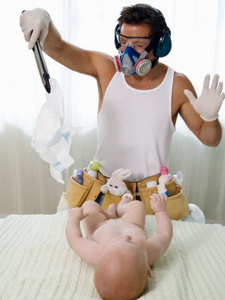Father Changing Baby's Diaper --- Image by © Paul Barton/Corbis