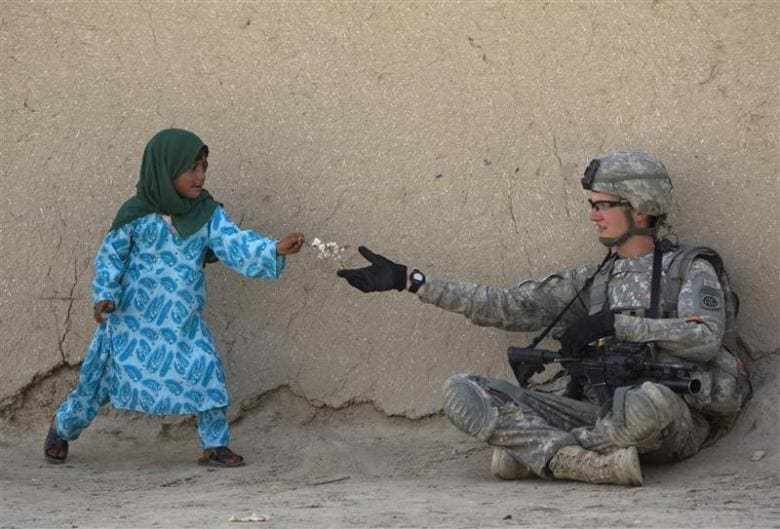 U.S. Army Private First Class Danny Comley of Camdenton Missouri, assigned to Delta Company 4th Brigade combat team,2-508, 82nd parachute infantry Regiment, receives flowers from an Afghan girl during a patrol in the Arghandab valley in Kandahar province, southern Afghanistan February 24, 2010. REUTERS/Baz Ratner (AFGHANISTAN - Tags: CIVIL UNREST CONFLICT IMAGES OF THE DAY)