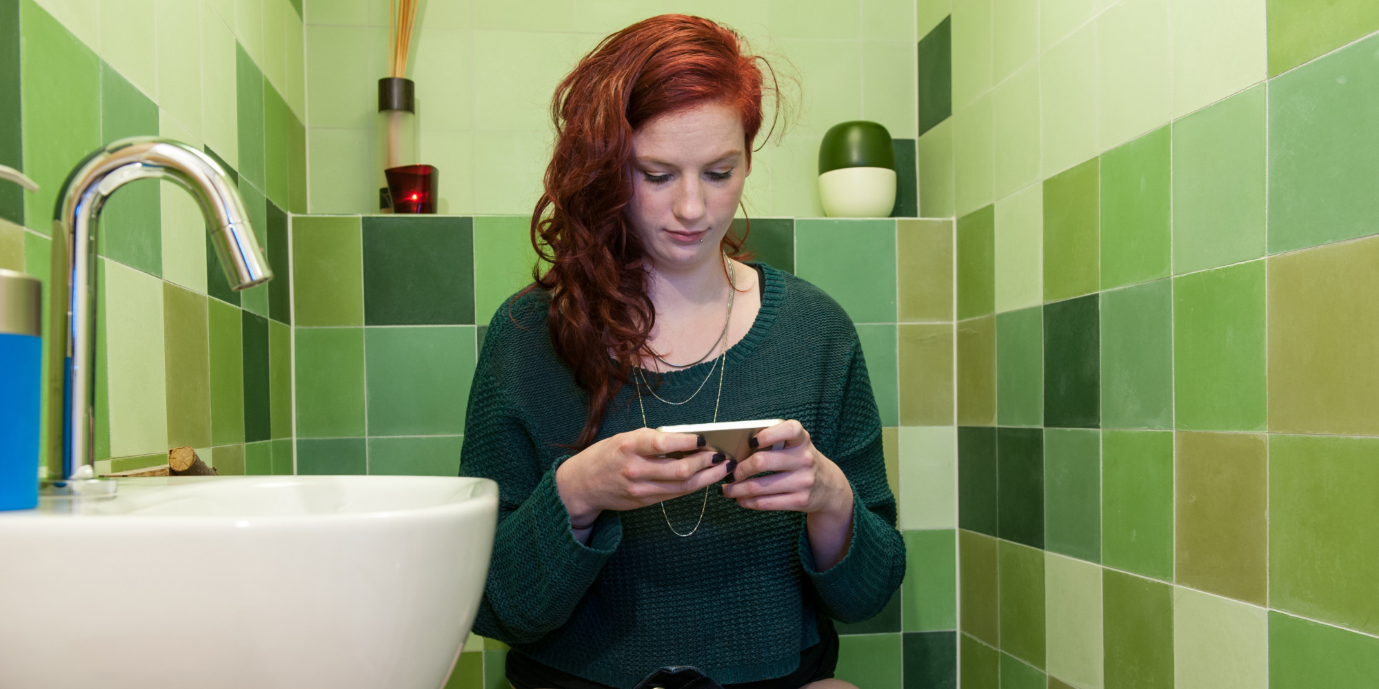 Young woman checking social media on the toilet