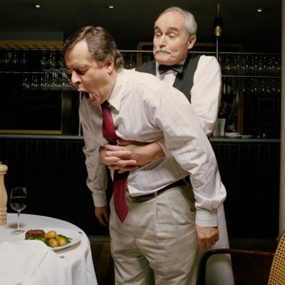 Waiter with arms around choking man's stomach in restaurant