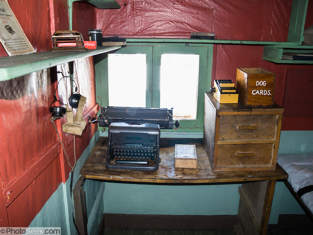 "In the Argentine Islands, Antarctica, Wordie House (1947-1954) has been restored and is designated under the Antarctic Treaty System as Historic Site and Monument No. 62. An old manual typewriter and ""dog cards"" bin rest on a desk. The United Kingdom first established meteorological research here as Base F or ""Argentine Islands"" on Winter Island in 1947. The main hut, built on the site of an earlier British Graham Land Expedition hut, was named after Sir James Wordie, a member of Shackleton's Imperial Trans-Antarctic Expedition who visited during its construction. The original main hut, ""Wordie House,"" now comprises the kitchen and bunk room. The base was extended in 1951 to include a generator shed, office, store, and toilet. A larger hut was built on nearby Galindez Island in 1954 and renamed Faraday Station in 1977. Researchers at Faraday Station shocked the scientific community by discovering the Antarctic ""ozone hole"" in 1985. Operational transfer to Ukraine in 1996 renamed Faraday Station to Vernadsky Research Base (Akademik Vernadsky)."