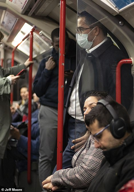 25281956-8055813-A_commuter_wearing_a_face_mask_on_the_central_line_tube_in_Londo-a-6_1582905695565